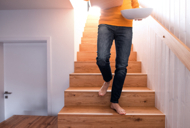 Person walking down the stairs barefoot with box and bowl